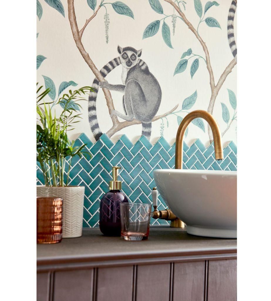 kúpeľňa s umývadlom na skrinke, modrým obkladom na stene a tapetou so vzorom lemurov