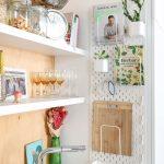 IKEA perforovaný organizér a otvorené biele poličky s pohármi a sklenenými nádobami nad kuchynským umývadlom