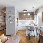 kuchyňa zariadená v bielo-sivej kombinácii z matno-lesklých povrchov, so zástenou a kuchynskou doskou z technického kameňa a pultíkom s vysokými stoličkami