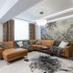 glamour obývačka s veľkometrážnou tapetou s motívom prírody, barokovým obkladom stien, kožušinami a koženou hnedou sedačkou