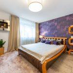 spálňa s fialovou vzorovanou tapetou, zariadená exotickým nábytkom z Indonézie, s masívnou posteľou a otvorenou skrinkou z ohýbaného lakovaného dreva, masívnymi drevenými kvetináčmi a krbom zaveseným na stene