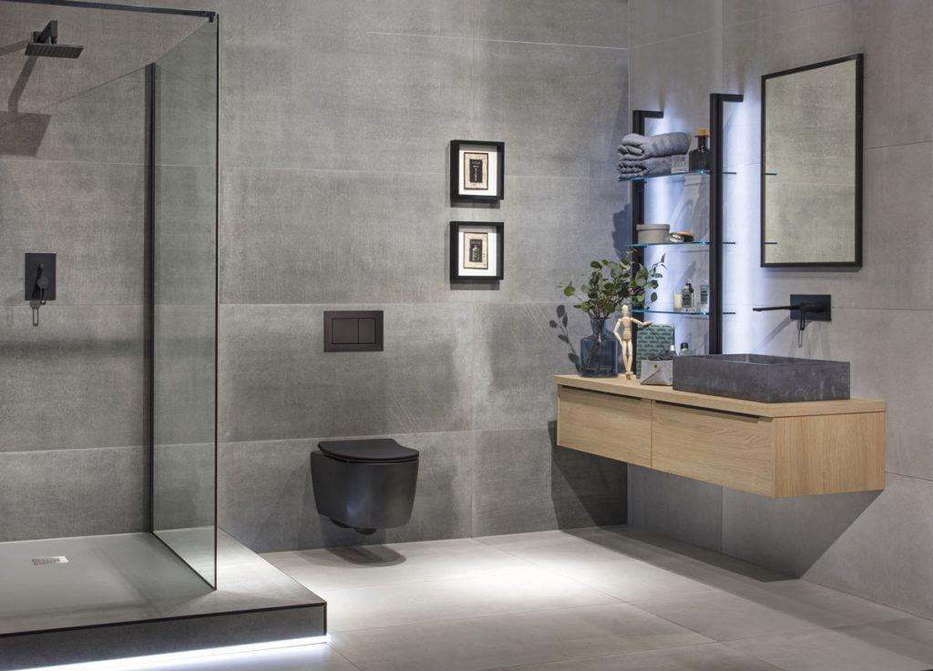 moderná minimalistická kúpeľňa spojená s WC, s veľkoformátovým sivým obkladom, sprchovacím kútom, betónovým umývadlom postaveným na drevených skrinkách a s otvorenými sklenenými policami
