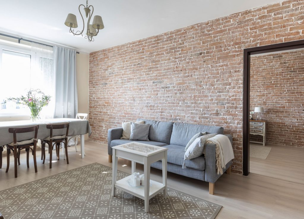 paneláková obývačka s jedálňou vo francúzskom vidieckom štýle, s originál tehlovou stenou