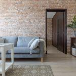 provance obývačka v paneláku s originál tehlovou stenou, sivým gaučom a vidieckym bielym stolíkom