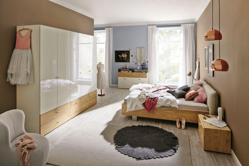 spálňa v modernom duchu, s dreveným nábytkom, pleteným kobercom a lesklými povrchmi
