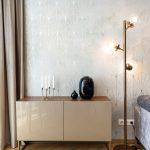 retro lesklý stolík so svietnikom a oválnou vázou, stojanovým kovovým osvetlením a tapetou v art déco štýle