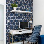 pracovňa s modrou vzorovanou stenou, modrým kresielkom a bielym stolíkom na zlatých nožičkách