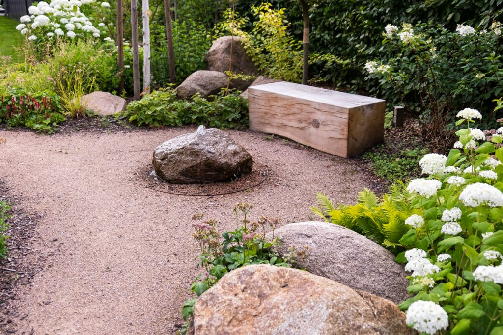 záhrada s krytou oddychovou časťou s lavičkou z dubového hranola a vodného prvku v podobe vody vyvierajúcej z kameňa