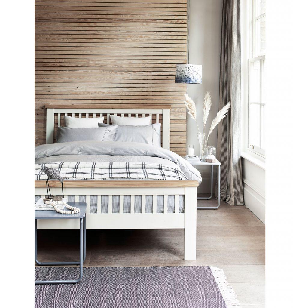 spálňa s drevenou bielo-hnedou posteľou a dreveným obkladom na stene