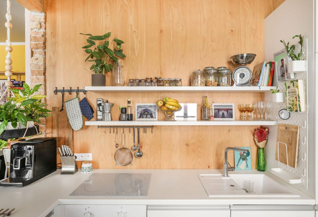 drevená zástena za kuchynskou linkou s bielymi otvorenými policami a IKEA perforovaným organizérom