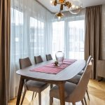 jedáleň v glam retro štýle s čalúnenými stoličkami, dreveným stolom a s dizajnovým osvetlením
