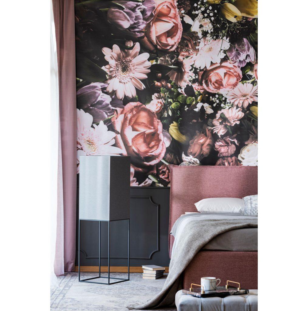 spálňa s kvetinovým vzorom na tapete v kombinácii s čiernou farbou na nábytku a s čalúnenou posteľou vo vínovej farbe