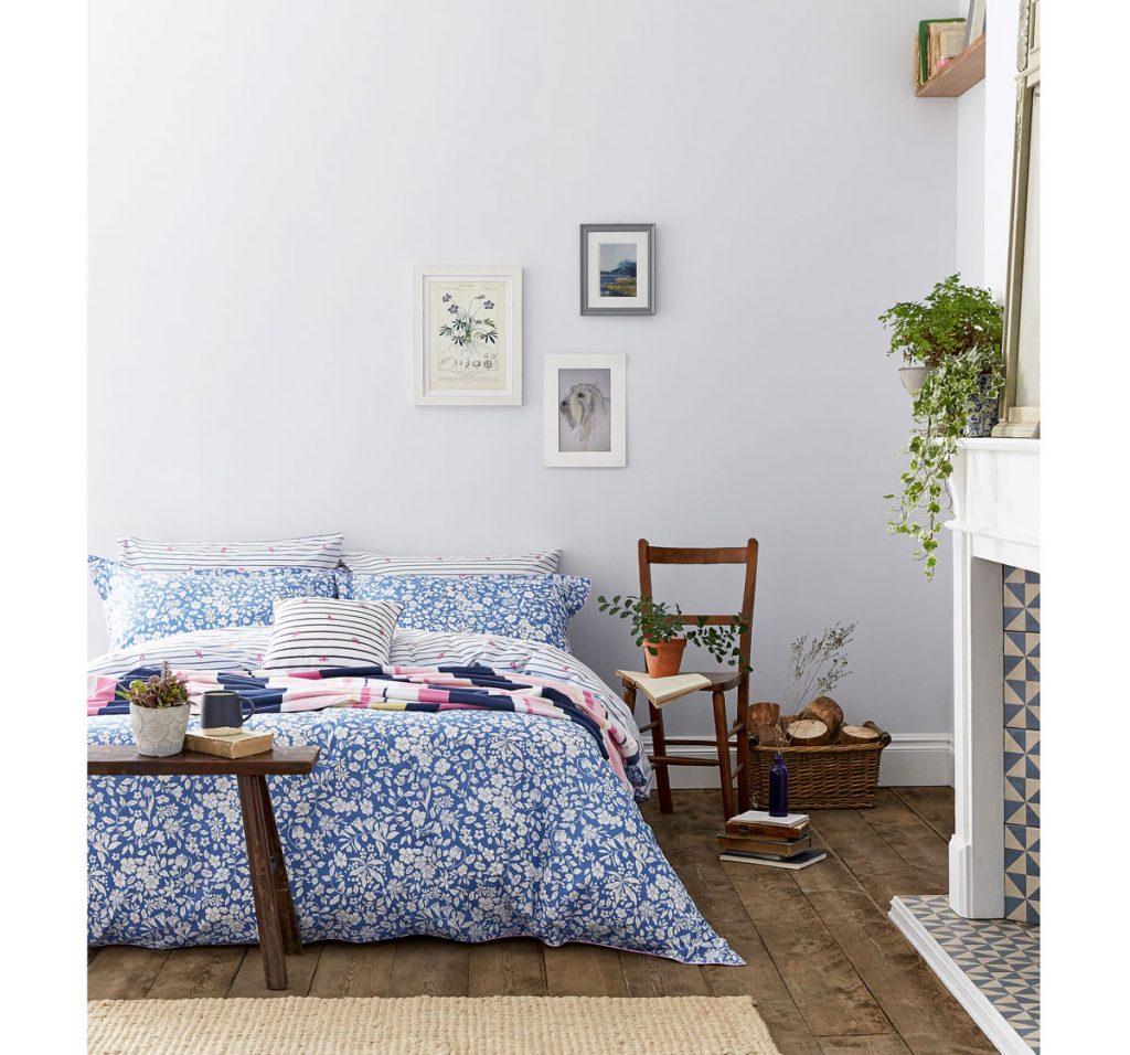spálňa vo vidieckom štýle v bielo-modrej kombinácii na textíliách a s dreveným nábytkom