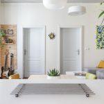 pohľad do interiéru s drevenými bielymi dverami, a obývačkou ladenou v svetlých farbách s farebnými akcentami