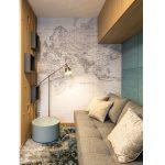 interiér s rozkladacou pohovkou, dizajnovým svietidlom, stolíkom, čalúnenou stenou, s textilnou tapetou mapy sveta a drevenou rebrinovou konštrukciou ako deliacim prvkom