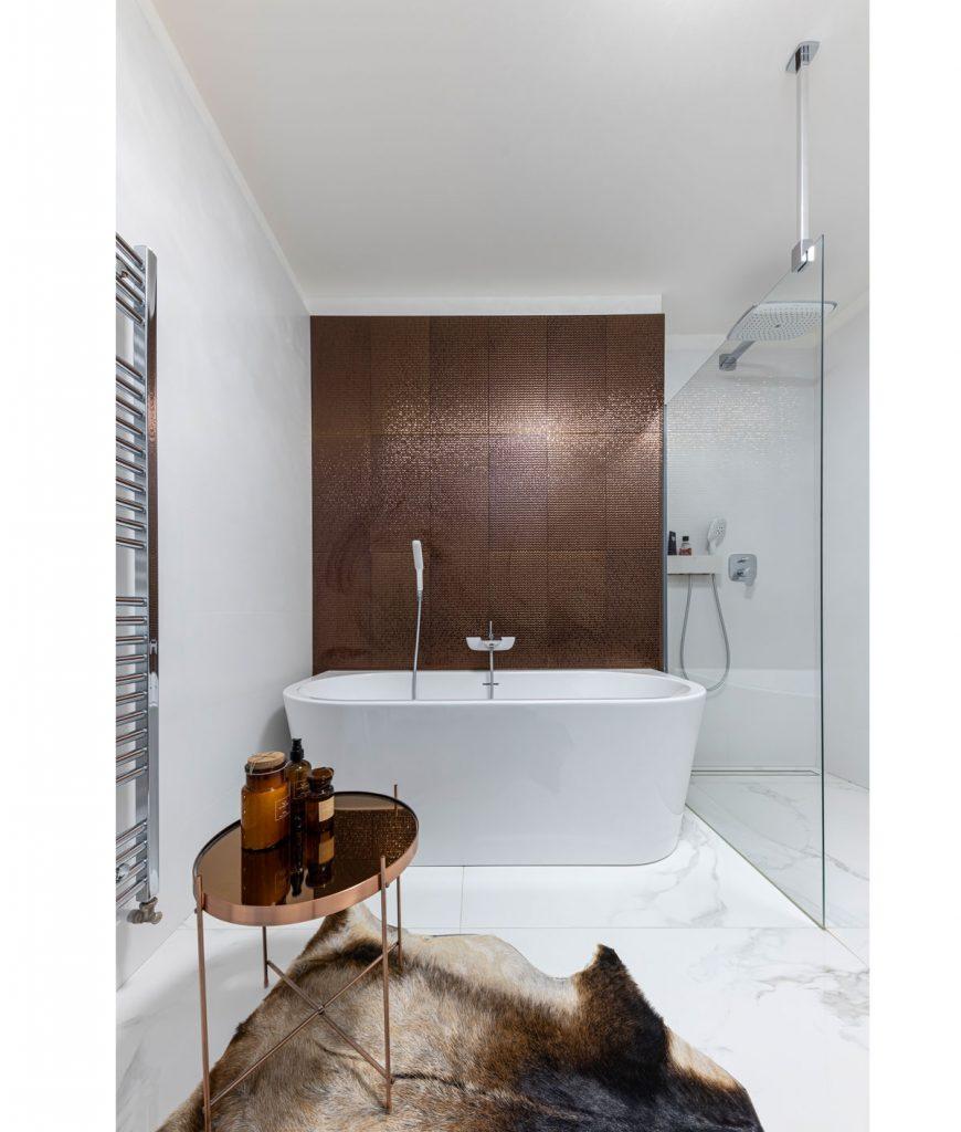 glamour kúpeľňa s obkladom metalického vzhľadu, so samostatne stojacou vaňou, sprchovým kútom, kožušinou a oválnym kovovým stolíkom