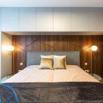 spálňa s posteľou, ktorá je umiestnená vo výklenku zo skriniek, s dreveným originálnym obložením, šatníková skriňa, príručná knižnica a retro stolové lampy