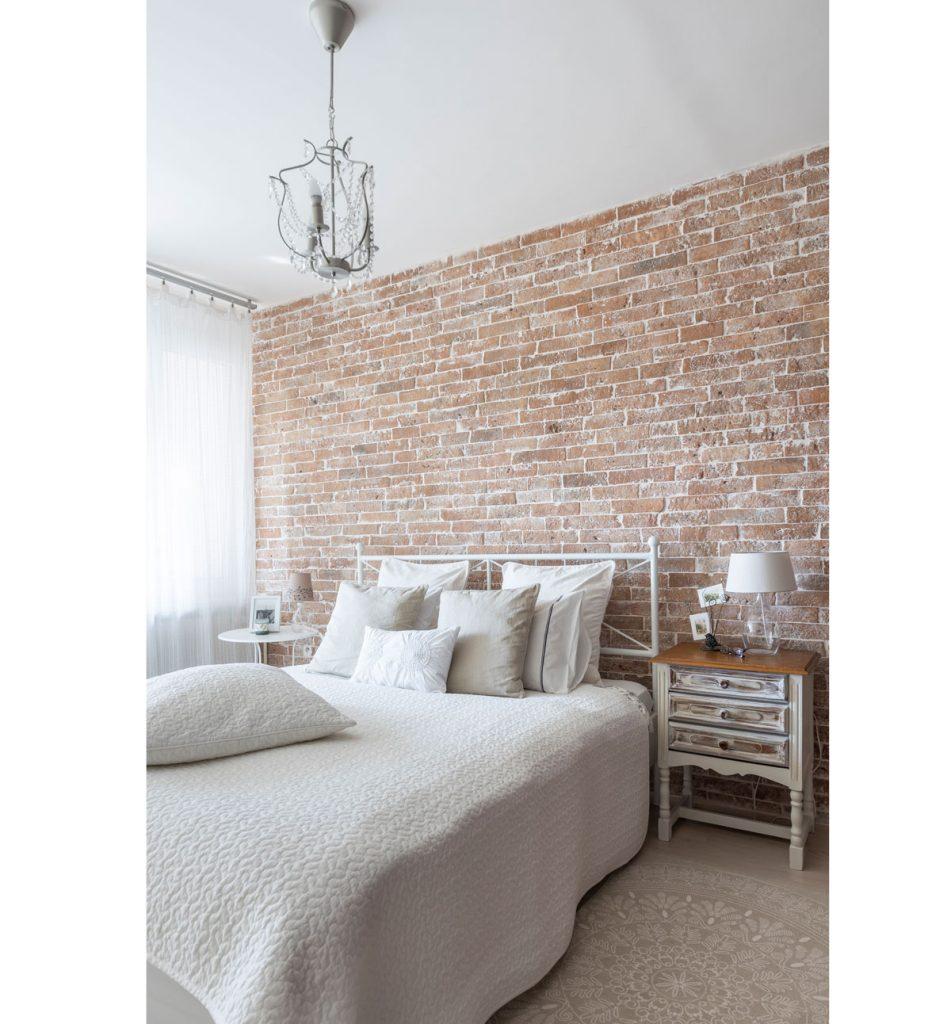 spálňa v provance štýle s originál tehlovou stenou a posteľou s bielymi textíliami
