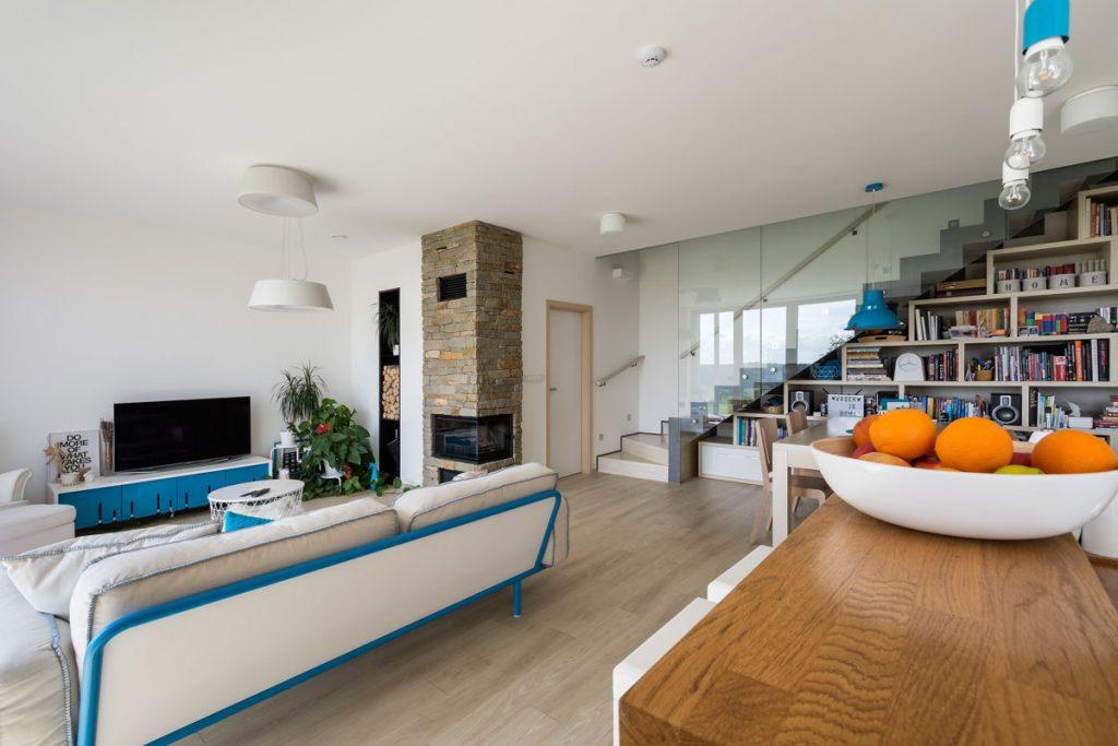 interiér rodinného pasívneho domu z pórobetónu s otvorenou obývačkou, jedálenským stolom, rohovým krbom a preskleným schodiskom