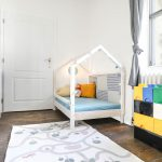 detská izba so smrekovou podlahou, bielymi skriňami, farebnou komodou v tvare Lega a drevenou posteľou v tvare domčeka