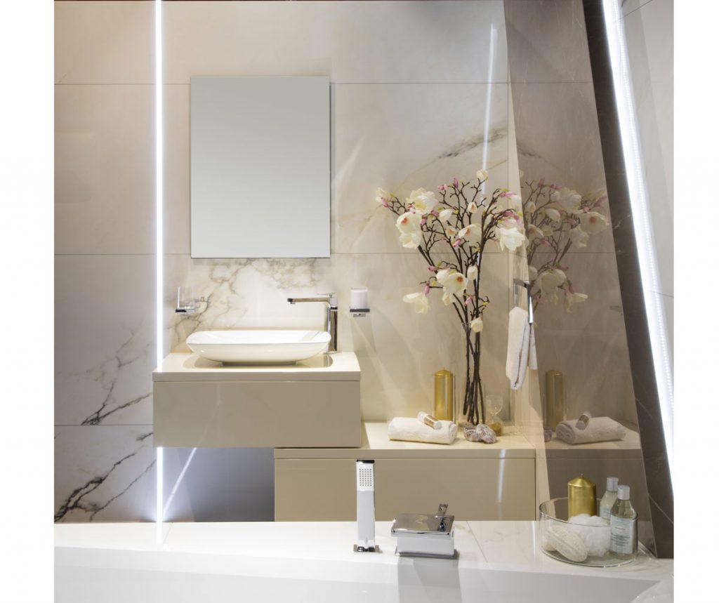kúpeľňa s mramorovým obkladom, s kvetinami vo váze, minimalistickými skrinkami bez úchytiek a jednoduchým umývadlom