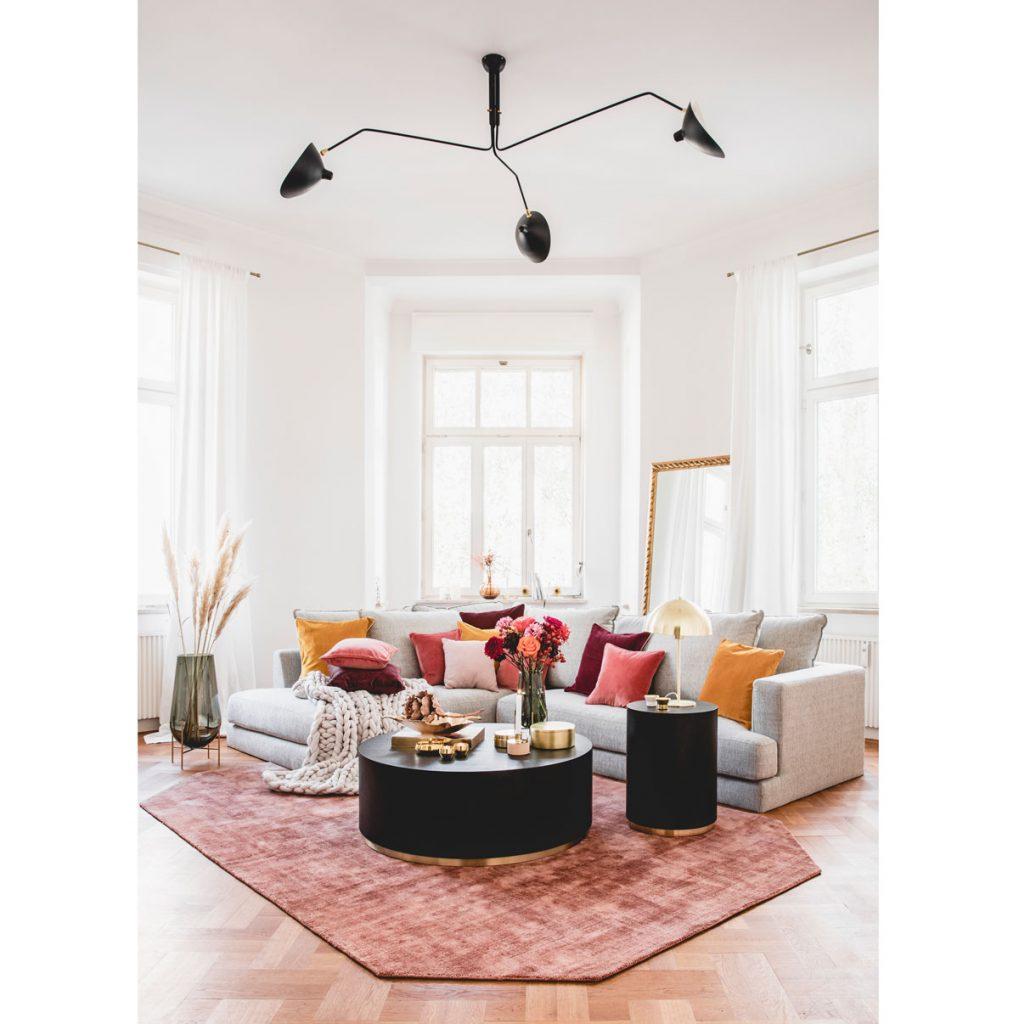 interiér so sivou sedačkou a vankúšmi v odtieňoch oranžovej a vínovej, s čiernymi okrúhlymi stolíkmi a kobercom vo farbe ružového vína