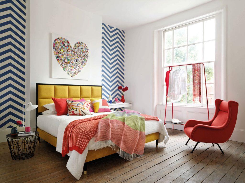 spálňa v pestrých farbách na textíliách, s červeným kreslom a štendrom na oblečenie a so vzorovanou stenou