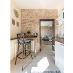 kuchyňa v provance štýle so stenou z pravých tehál, pultíkom a vysokou drevenou stoličkou