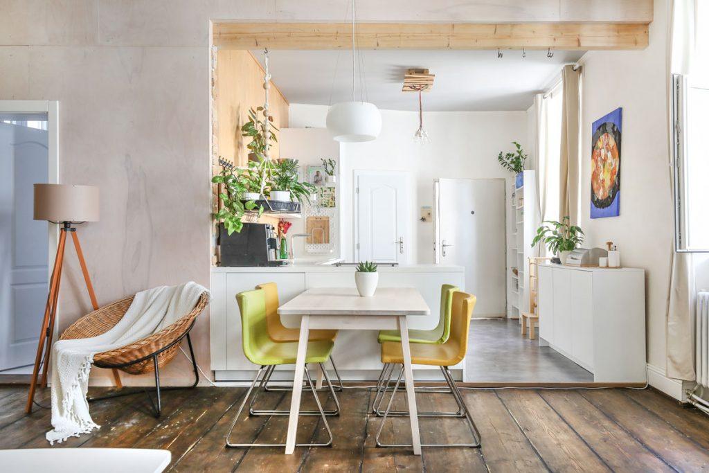 zrekonštruovaný starý svetlý byt so smrekovou podlahou, prúteným kreslom, stojacou lampou, jedálenským stolom a farebnými stoličkami, a s kuchyňou, ktorá je priestorovo oddelená skrinkami