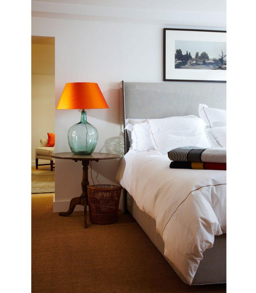 spálňa v neutrálnych farbách oživená oranžovou farbou na lampe