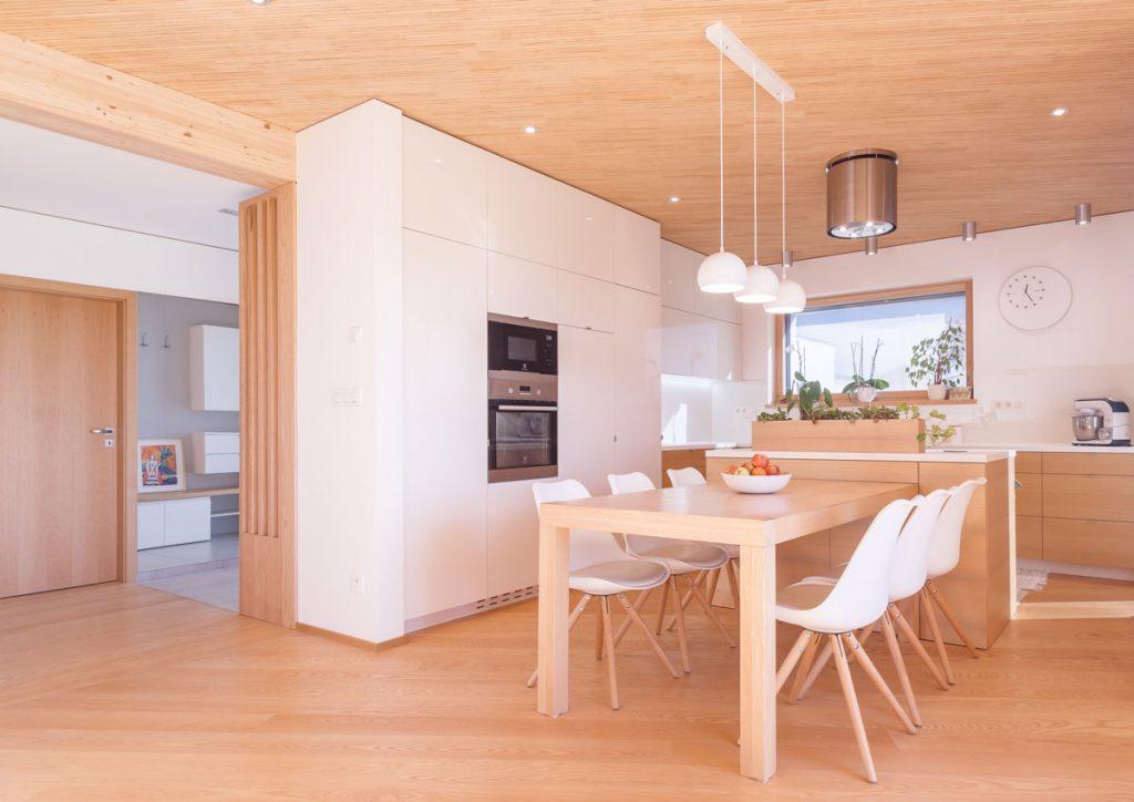 kuchyňa v drevodome s jedálenským stolom zariadená v dreve, so vstavanými spotrebičmi