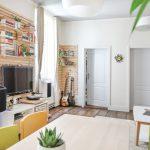 interiér presvetleného bytu s drevenými rebrinami, na ktorých sú zavesené police a TV