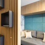 drevená rebrová konštrukcia oddeľujúca miestnosť na relax a spanie s rozkladacou pohovkou a čalúnenou stenou