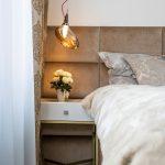 glamour spálňa s bielym nočným stolíkom, netradičným svietidlom a čalúneným čelom postele