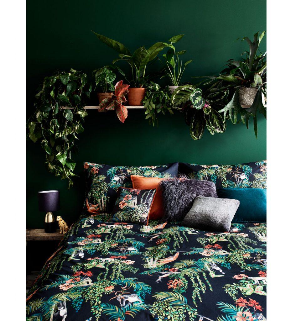 spálňa v tmavých odtieňoch modrej a zelenej, s prírodnými motívmi na obliečkach a kvetinami na polici nad posteľou