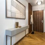 predsieň s drevenou šatníkovou zástenou, minimalistickým látkovým obrazom a odkladacím priestorom na kovových nožičkách