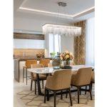 jedáleň prepojená s kuchyňou v minimalistickom štýle, v jedálni je stôl s kamennou doskou a mohutné čalúnené stoličky v pieskovohnedej farbe