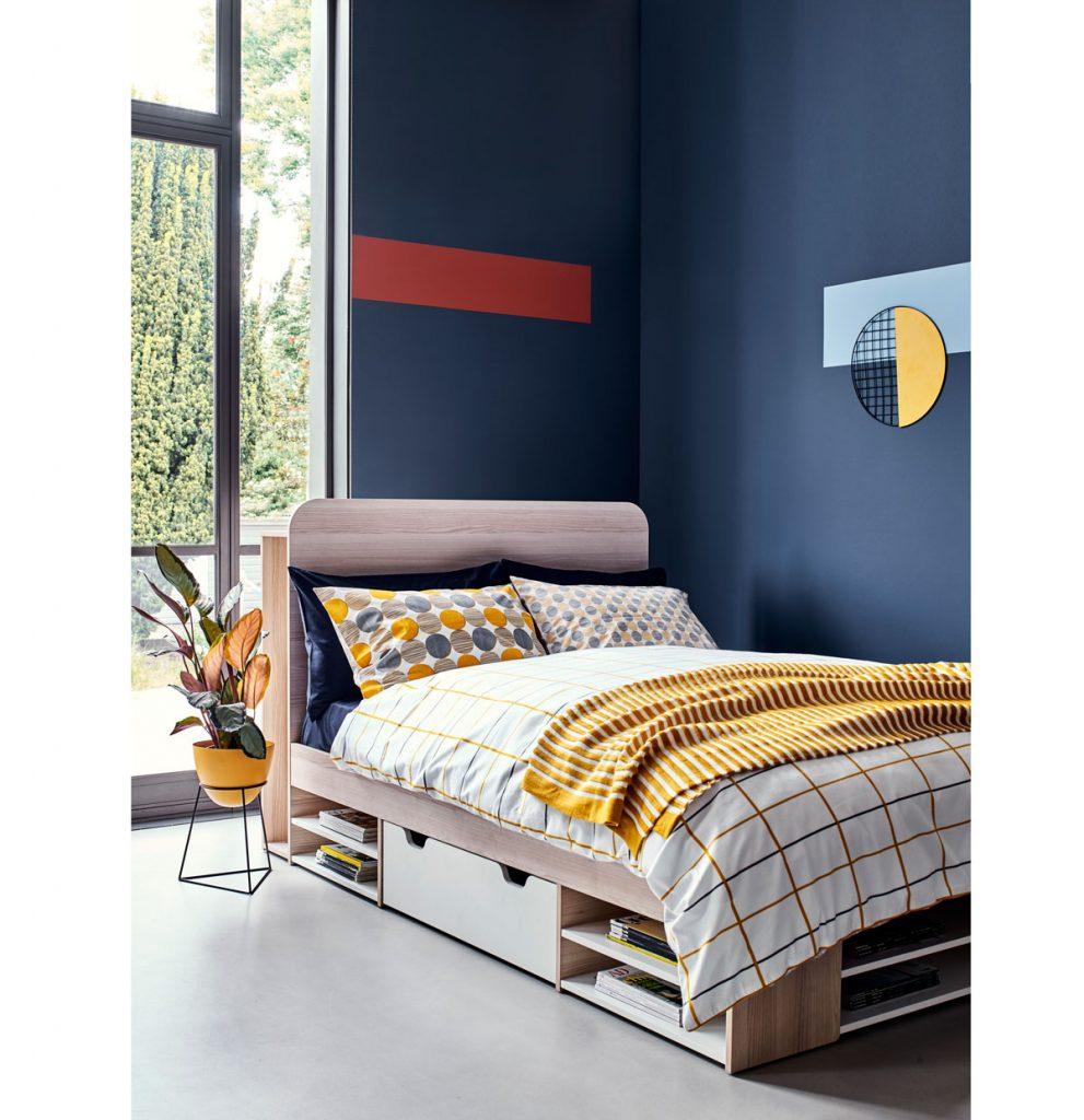 spálňa s geometrickými vzormi na stenách a obliečkach