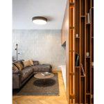 obývačka s pohovkou v metalickom odtieni, okrúhlym stolíkom, drevenou podlahou a TV stenou v lesklých a matných povrchoch