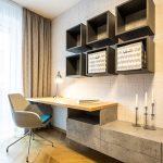 detská izba s písacím stolom plynule prechádzajúcim do skriniek a s odkladacími priestormi v podobe políc a s textilnou neutrálnou tapetou na stene