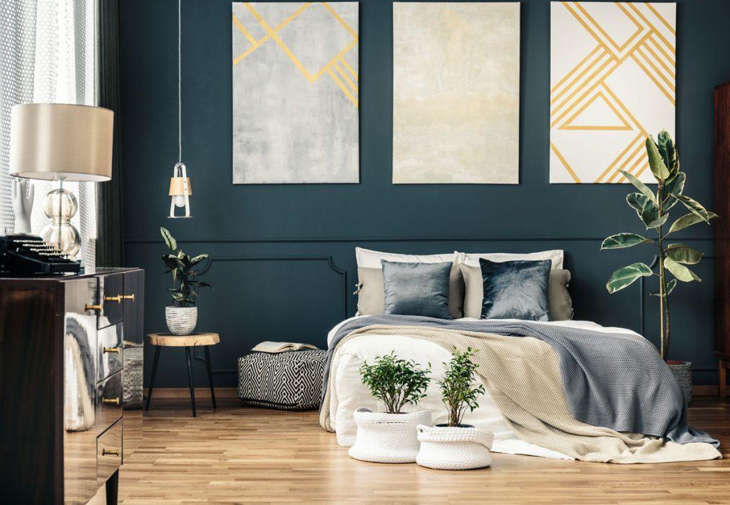 glamour spálňa s lesklou skrinkou, s kvetinami v pletených obaloch, geometrickými obrazmi a posteľou s textíliami v sivej, béžovej a bielej farbe