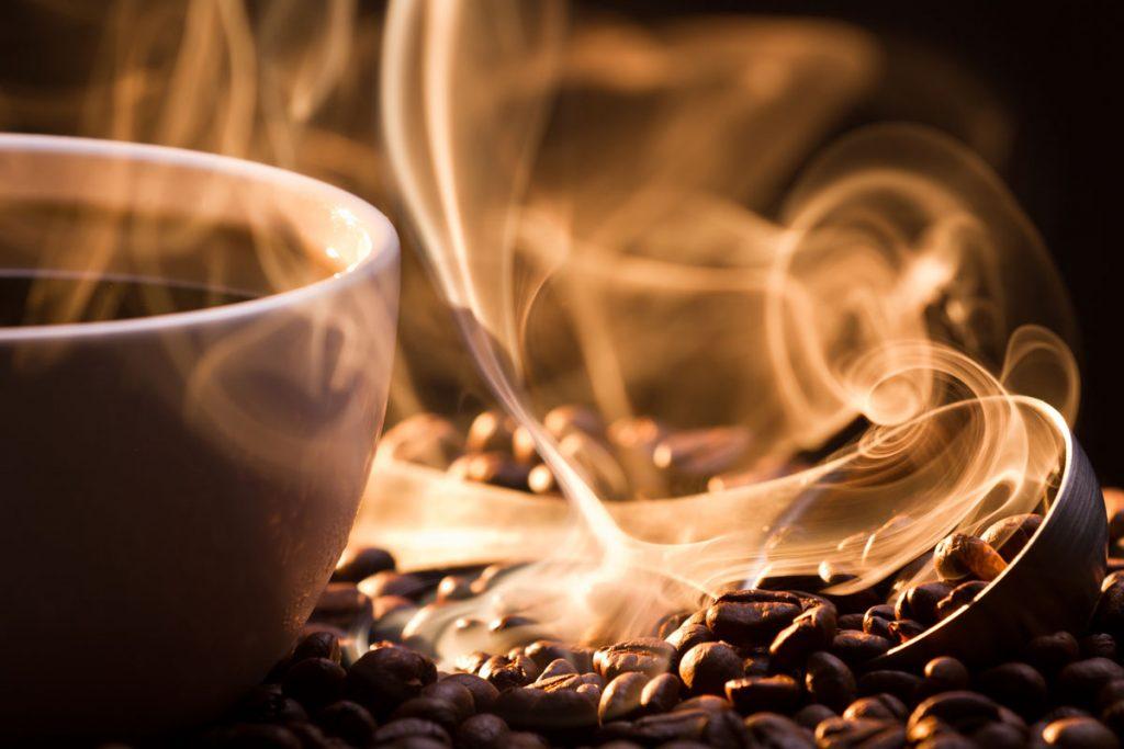 šálka kávy s praženými kávovými zrnkami