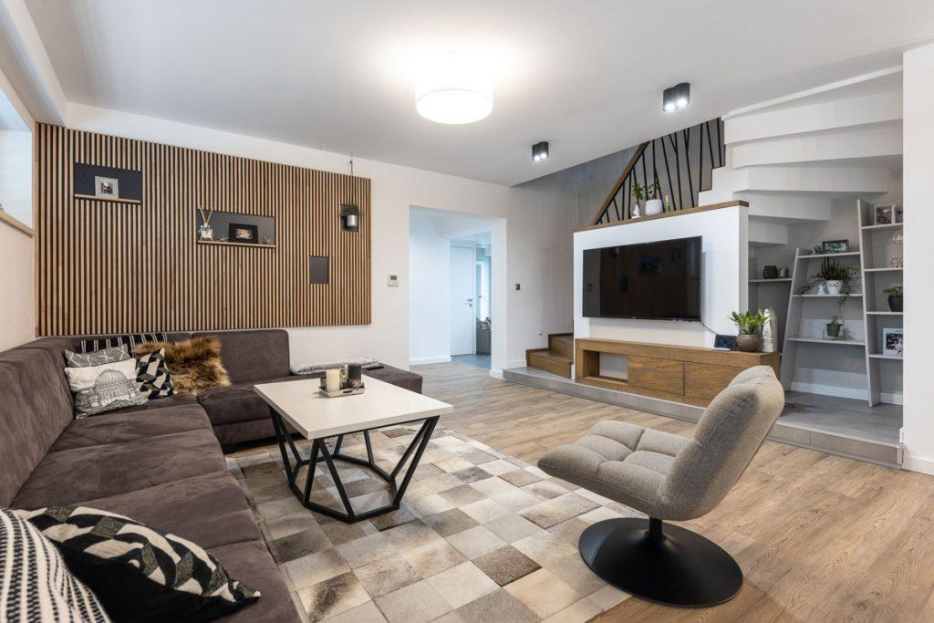 minimalisticky a industriálne ladená obývačka s rohovou sedačkou, kovovým stolíkom, otáčacím kreslom, drevenou TV stenou umiestnenou pod schodiskom a rebrovým dreveným obložením steny