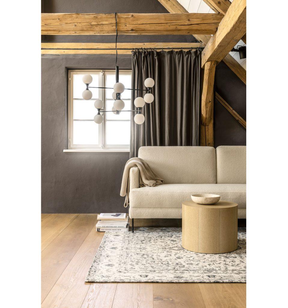 interiér v minimalistickom natur štýle s neutrálnou pohovkou, okrúhlym dreveným stolíkom, tkaným kobercom a sivými závesmi