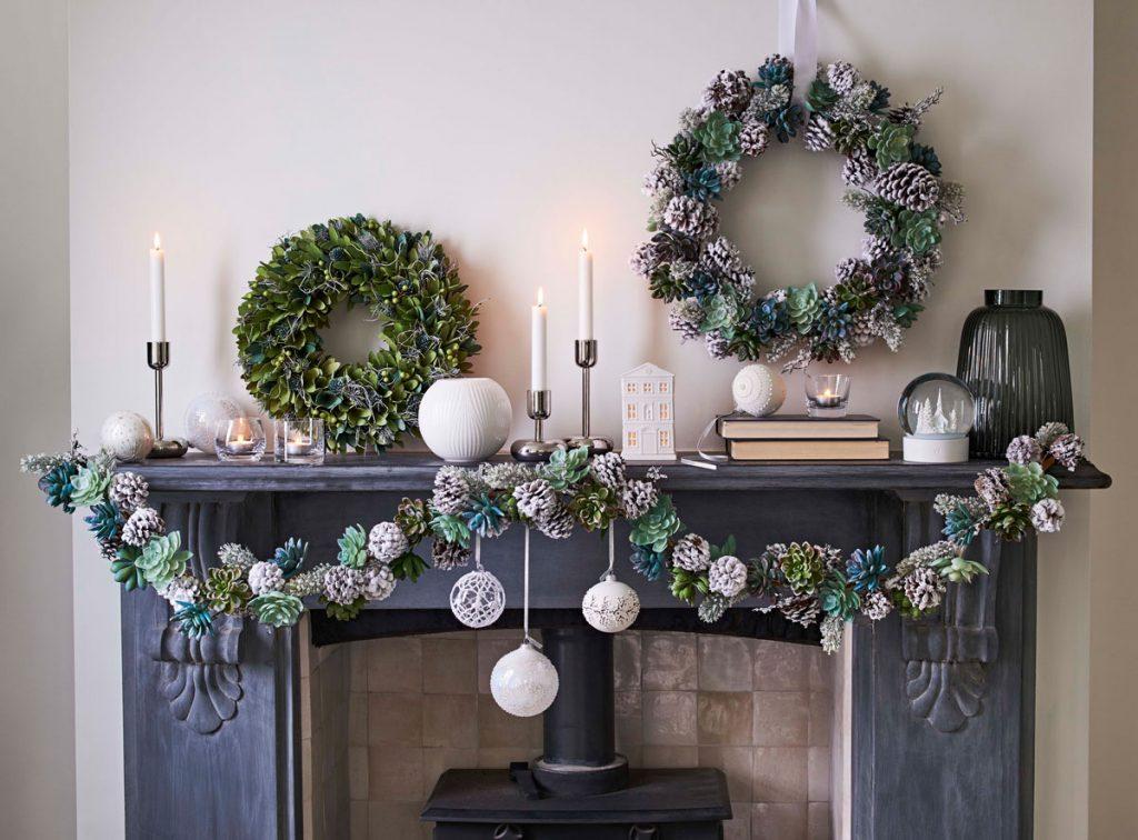 vianočná závesná výzdoba kozubovej rímsy zložená zo šiškovej girlandy, na ktorej sú zavesené vianočné biele gule a so šiškového venca zaveseného nad rímsou