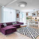 obývačka spojená s kuchyňou, s masívnou drevenou knižnicou, fialovou pohovkou a vzorovaným kobercom a jedálenským stolom, ostrovčekom a kuchynskou linkou vo vidieckom štýle s industriálnymi prvkami