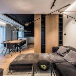 obývačka prepojená s jedálňou a kuchynskou časťou v modernom minimalistickom štýle, celý interiér je zariadený v prírodných materiáloch, v kuchyni s čiernym stropom a bielou kuchynskou linkou, v jedálni s veľkým dreveným stolom a čiernymi stoličkami, v obývačke s čiernou pohovkou