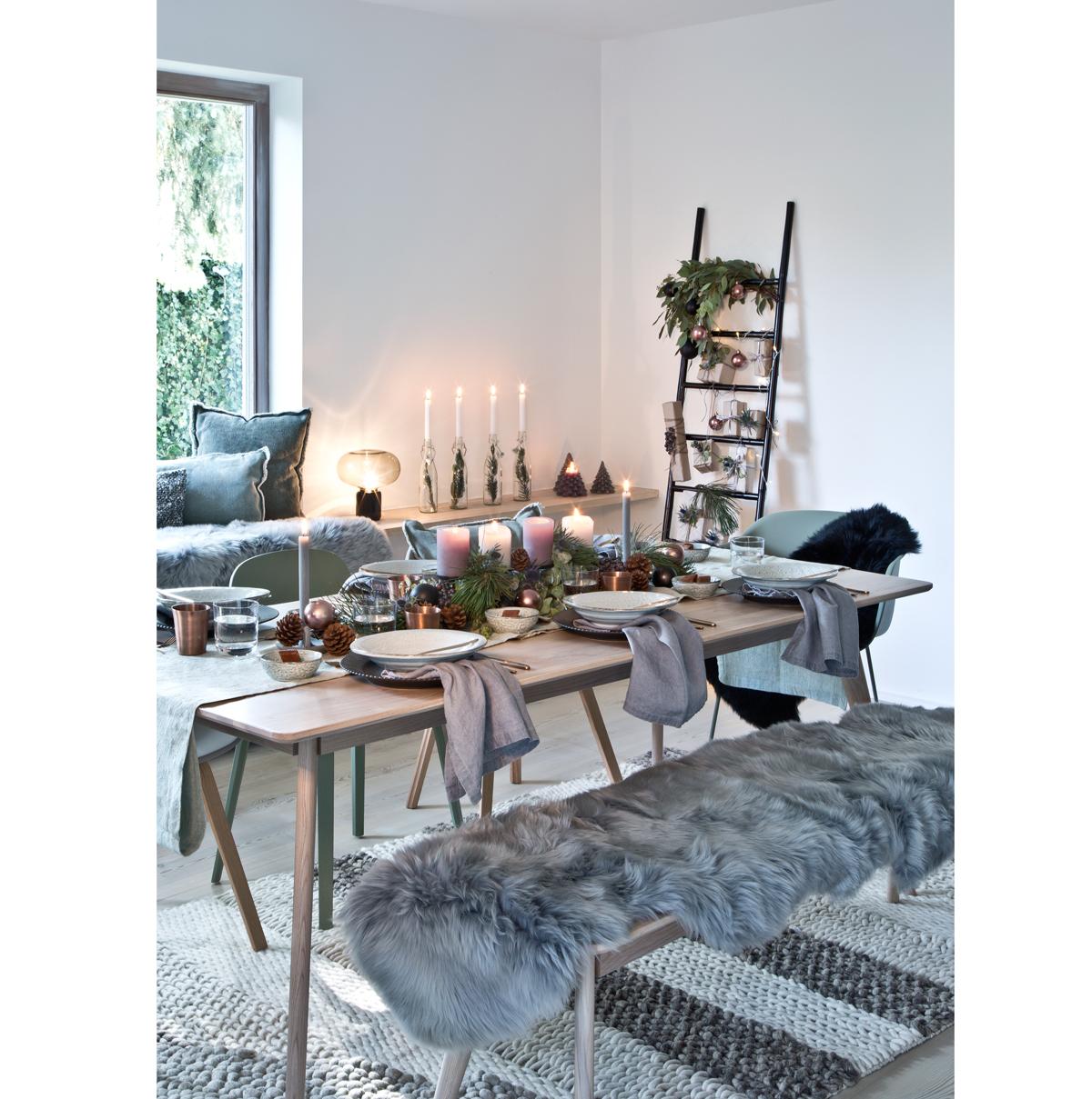 sviatočne prestretý stôl s adventným vencom, sviečkami a taniermi,, pri stole je drevená lavica s kožušinou