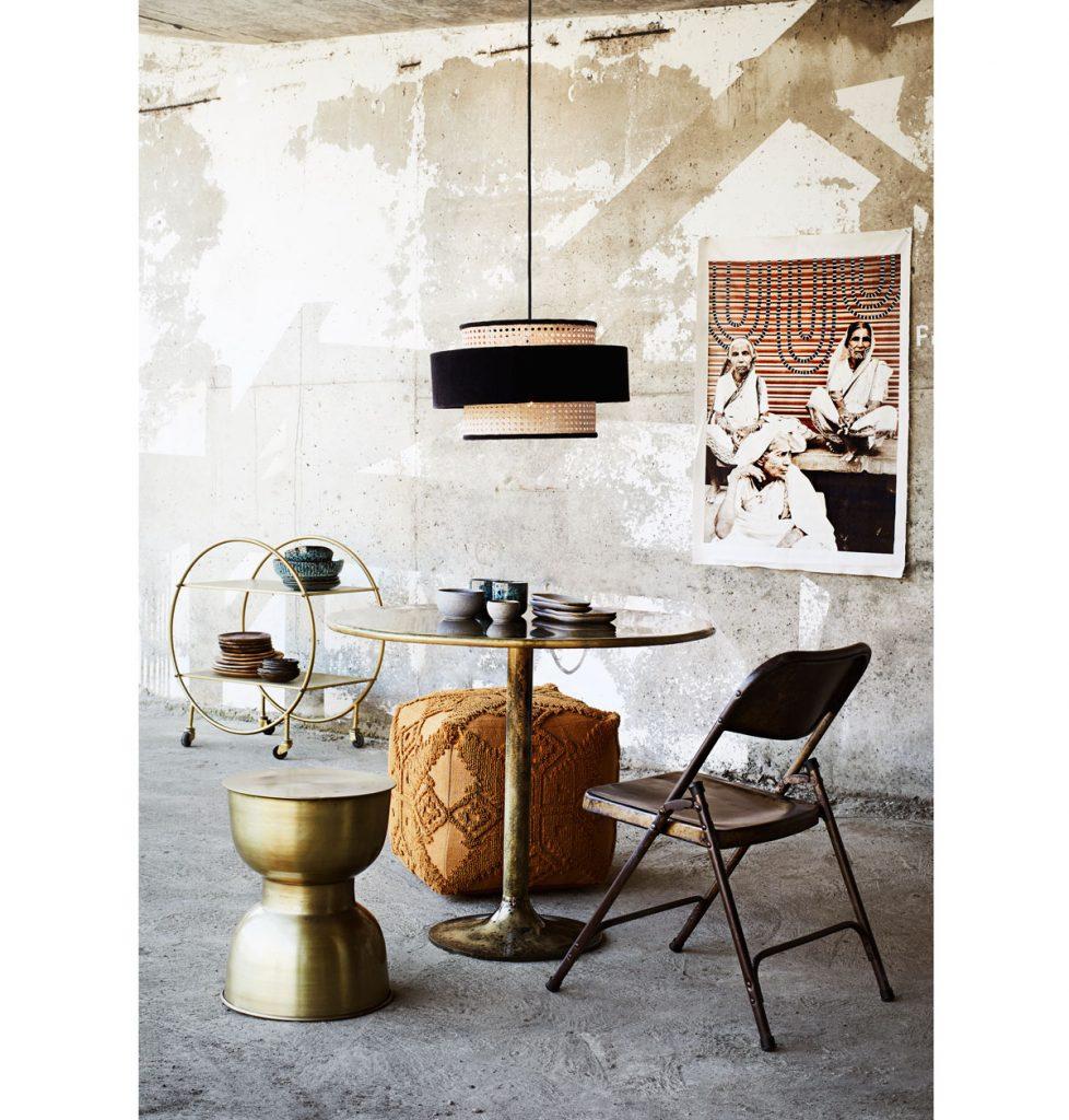 industriálny interiér s betónovou podlahou, kovovým mosadzným stolíkom a skladacou stoličkou, stropným pleteným svietidlom a pleteným taburetom v tvare kocky zdobeným orientálnym motívom