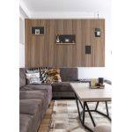 interiér v industriálnom štýle s tmavou sedačkou, kovovým stolíkom kombinovaným s drevom, kobercom z kože a drevenou rebrovou stenou